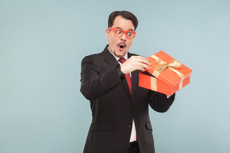Surprised man in black suit holding red gift box and looking inside with excited face. Studio shot, isolated on light blue background Stock Photo
