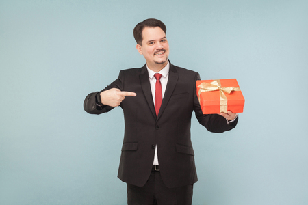 Happy man in black suit holding and pointing red gift box. Studio shot, isolated on light blue background