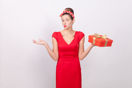 Confused, puzzled cute woman holding box, say dont know. Indoor, studio shot, isolated on gray background