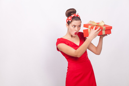 Cunning woman, looking inside gift box . Indoor, studio shot, isolated on gray background Stock Photo