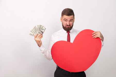 Business man pay for big love, holding many dollars. Indoor, studio shot, isolated on gray background