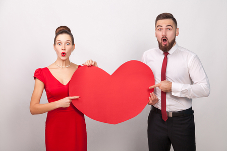 Wow! Big love. Wondered couple pointing fingers at red heard. Indoor, studio shot, isolated on gray background Banco de Imagens