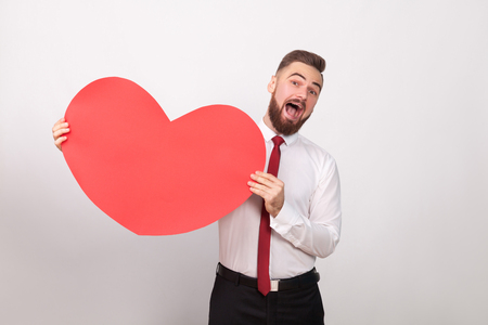 Funny businessman toothy smiling, holding big red heart. Indoor, studio shot, isolated on gray background