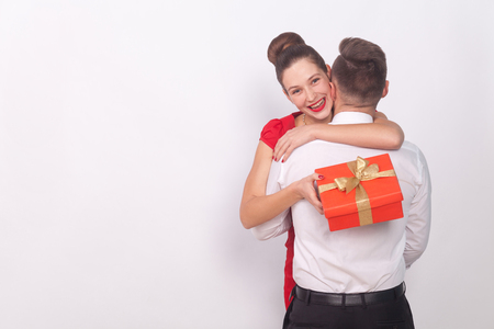 Happy girl has received a gift, toothy smile, embrace her man. Indoor, studio shot, isolated on gray background