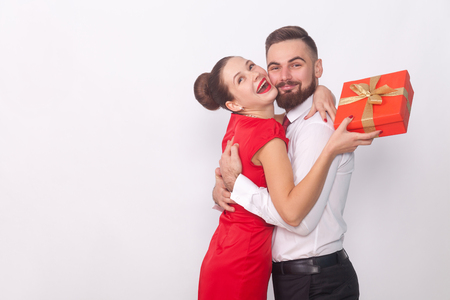 Its present for you! Couple hugging, woman holding gift box. Indoor, studio shot, isolated on gray background