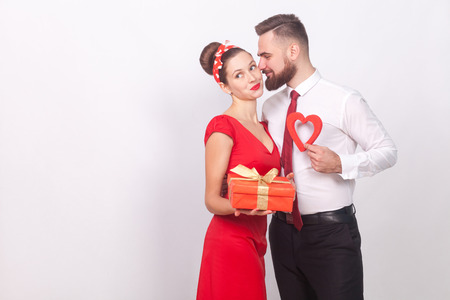 Man present gift box his love in valentines day. Indoor, studio shot, isolated on gray background Reklamní fotografie