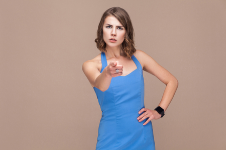 Im choosing you! Well dressed woman pointing finger at camera. Indoor shot on light brown background Stok Fotoğraf