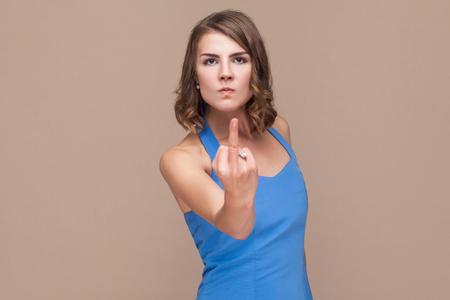 Fuck off! Bad girl showing fuck sign at camera. Studio shot