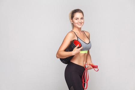Cute professional instructor holding foam roller and ready to massage. Studio hot, isolated on light gray background