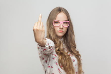 Unhappy woman, showing fuck sign at camera. Focus on hand. Indoor shot, gray background