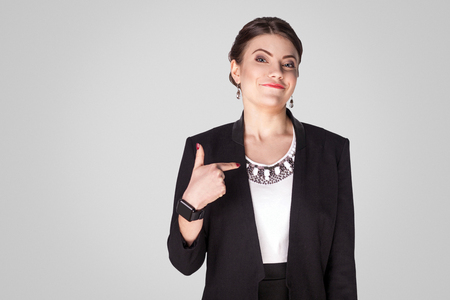 Proud, airy businesswoman pointing finger himself and toothy smile. Studio shot, indoor. Isolated on grey background