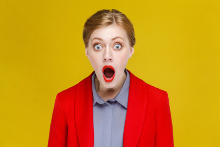 Wow! Red head woman in red suit amazement. Studio shot, isolated on yellow background