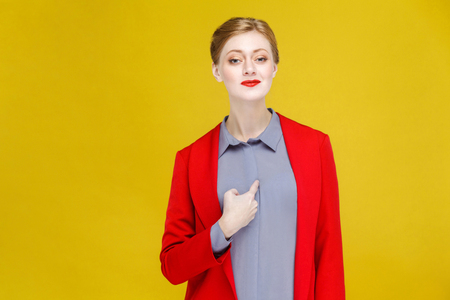Proud ginger red head business woman in red suit pointing himself. Studio shot, isolated on yellow background