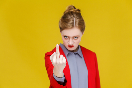 Angry business woman in red suit demonstrate fuck you sign. Studio shot, isolated on yellow background