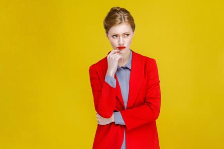 Thoughtful confident business woman thinking. Studio shot, isolated on yellow background Stockfoto