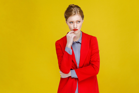 Thoughtful confident business woman thinking. Studio shot, isolated on yellow background 免版税图像