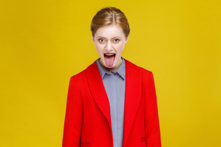 Crazy woman tongue out . Studio shot, isolated on yellow background Stock Photo