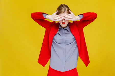 No! Red hair business woman in red suit closed eyes. Studio shot, isolated on yellow background Stock Photo