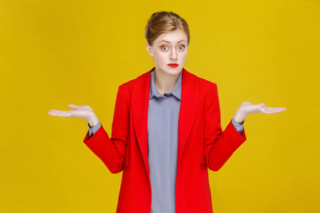 I don't know! Confused business woman looking at camera. Studio shot, isolated on yellow background
