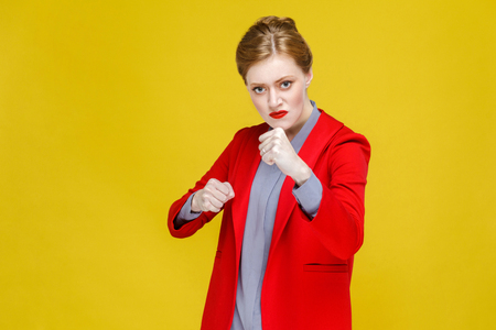 Aggressive angry fashion woman in suit boxing at camera. Studio shot, isolated on yellow background