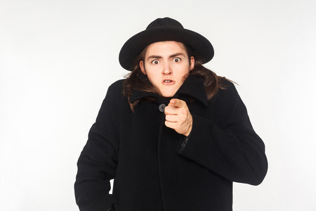 Funny man in coat pointing finger at camera and have a shocked look. Studio shot
