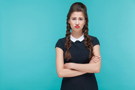 Unhappy depressed girl looking at camera with stress look. Indoor, studio shot on blue background Stockfoto