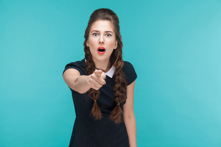 Surprised young woman pointing finger at camera and shocked. Indoor, studio shot on blue background