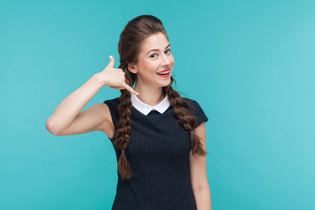 Call me! Pretty woman looking at camera, smiling and showing phone sign. Studio shot, blue background 스톡 콘텐츠