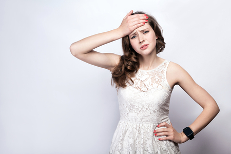 Portrait of beautiful woman with freckles and white dress and smart watch with headache pain on silver gray background. healthcare and medicine concept.