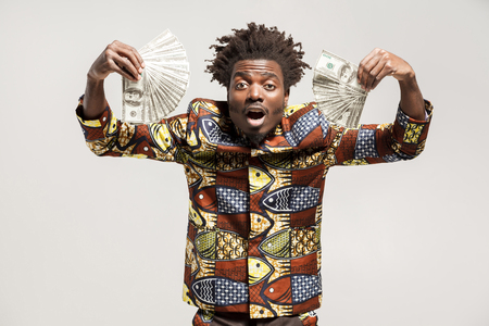 Wow! Surprised afro businessman holding many dollars and so happy. Indoor, isolated on gray background