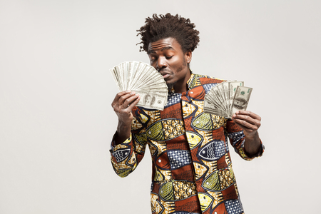 Sniff in pleasure. African man closed eyes , holding his money. Indoor, isolated on gray background