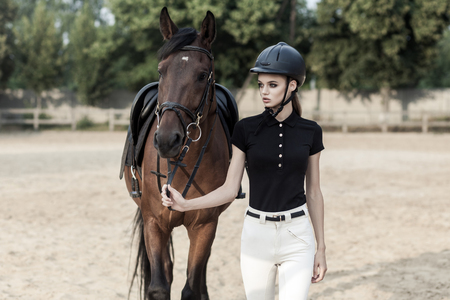 Rider and horse go to the country after the race. Outdoor shot, sport and fashion concept.