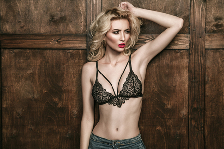 attractive blonde woman in black lace brassiere posing on wooden brown background 스톡 콘텐츠