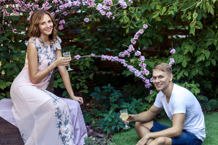 Young adult man says a toast. Holding Champagne glass, toothy smiling. Outdoor shot, spring park or summer concept. Love, sensual people