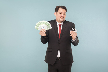 Businessman can not choose, online banking or money on his hands. Indoor, studio shot, isolated on light blue or gray background 写真素材