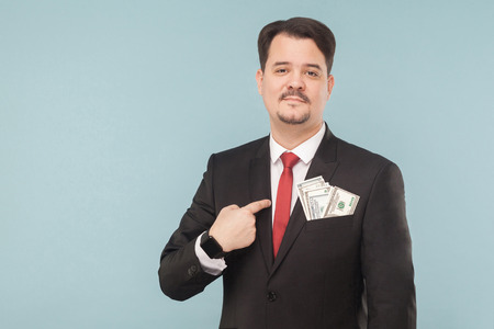 Businessman pointing finger at himself money in the pocket. Indoor, studio shot, isolated on light blue or gray background