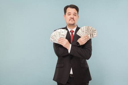 Portrait of cool wealthy successful businessman. Indoor, studio shot, isolated on light blue or gray background