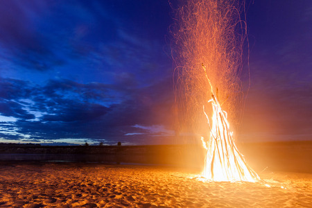 big bright bonfire on sandy beach at night