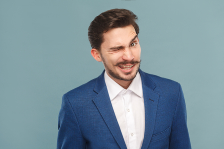 Funny businessman wink and flirt at camera. Business people concept, richly and success. Indoor, studio shot on light blue background
