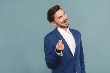 Give me money. Foxy businessman toothy smiling . Business people concept, richly and success. Indoor, studio shot on light blue background Foto de archivo