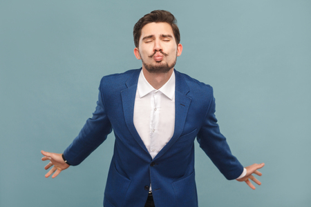 Man in suit send air kissing. Business people concept, richly and success. Indoor, studio shot on light blue background Archivio Fotografico
