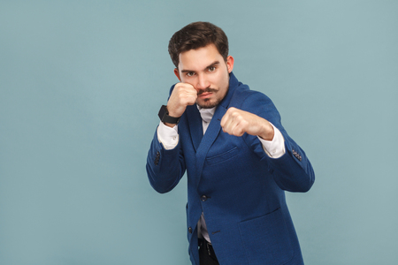 Dangerous man boxing at camera. Business people concept, richly and success. Indoor, studio shot on light blue background