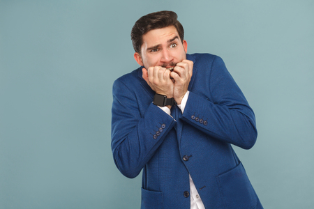 Business man very scared and stressed. Business people concept, richly and success. Indoor, studio shot on light blue background