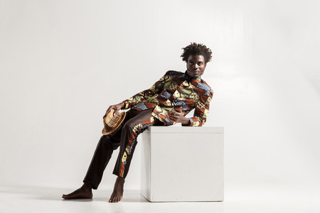 Barefooted african man uncomfortble sit on coub. Indoor, isolated on gray background