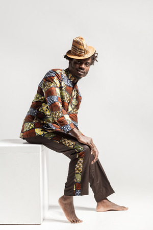 Happy fashion afro man in traditional clothes sit on coub . Indoor, isolated on gray background