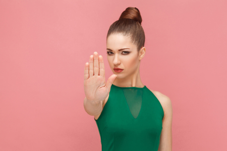 Hand ban, no! Woman showing hand, stop sign. Expression emotion and feelings concept. Studio shot, isolated on pink background