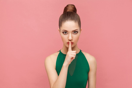 Woman showing shh, silence sign. Expression emotion and feelings concept. Studio shot, isolated on pink background