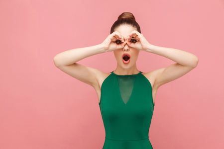 Binoculars sign. Woman looking far far away. Expression emotion and feelings concept. Studio shot, isolated on pink background
