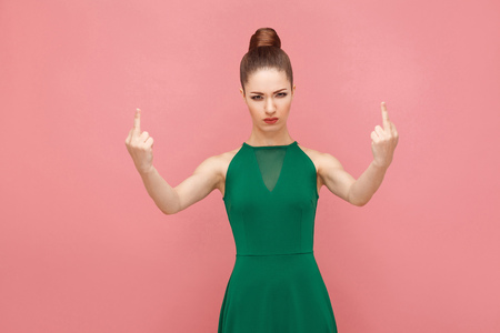 Fuck all! Woman showing bad sign at camera. Expression emotion and feelings concept. Studio shot, isolated on pink background