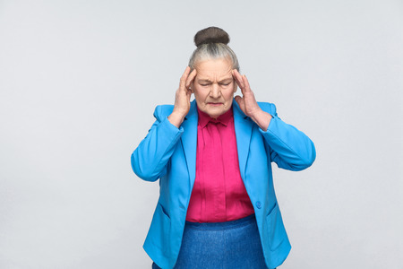 Aged woman have migraine and headache pain. Portrai of expressive grandmother with light blue suit and pink shirt standing with collected bun gray hair. Studio shot, isolated on gray background Stock Photo